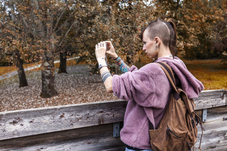 Woman photographing while standing at park