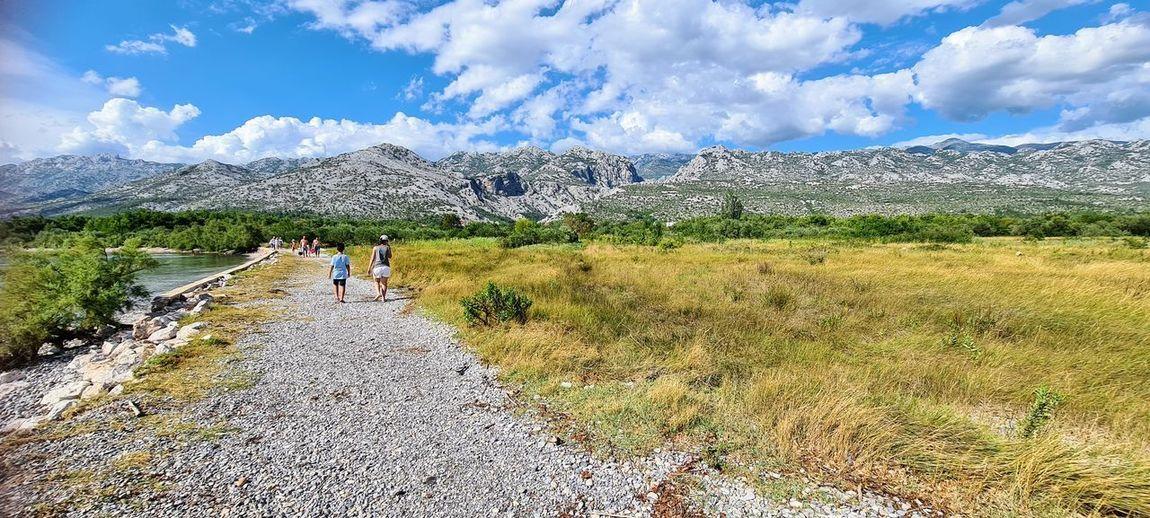 People walking on landscape against sky