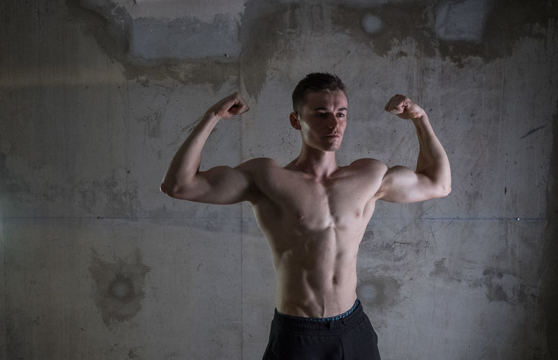 Young man flexing muscles against wall