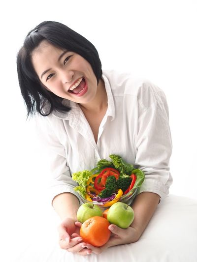 Asian woman joyful with fresh vegetables salad. Asian Woman Cheerful Day Food Food And Drink Freshness Front View Fruit Happiness Healthy Diet Healthy Eating Healthy Lifestyle Indoors  Lifestyles One Person People Portrait Real People Smiling Studio Shot Toothy Smile Vegetable White Background Young Adult Young Women