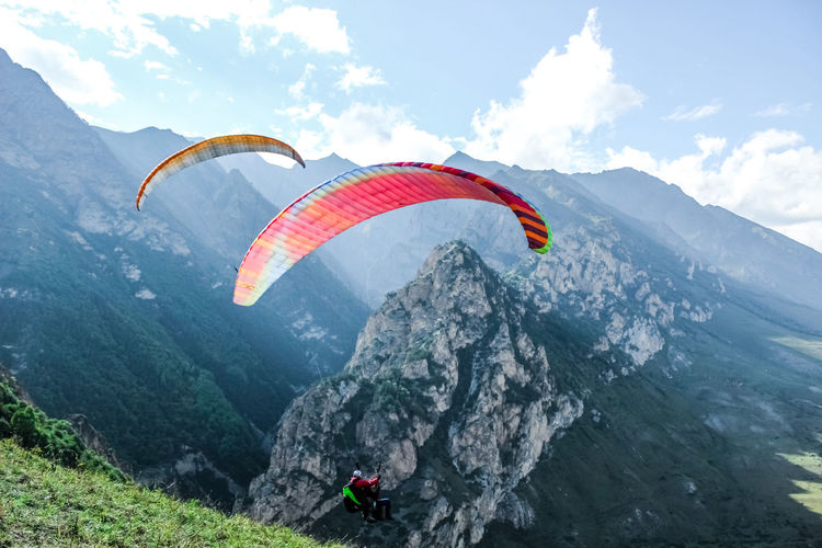 People paragliding on mountain peak against sky