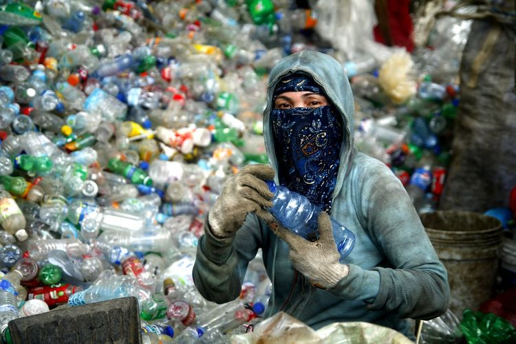 Worker at a materials recovery facility segregate recyclable materials ASIA Asian  Philippines Filipino Work Working Job Worker Recycle Recycling Reuse Materials Recovery Facility Waste Waste Management Trash Dirt Dirty Garbage Junk Junkyard Segregated Plastic Plastic Bottle