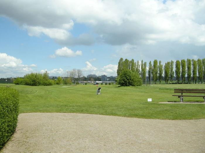 Golf bag on course against sky
