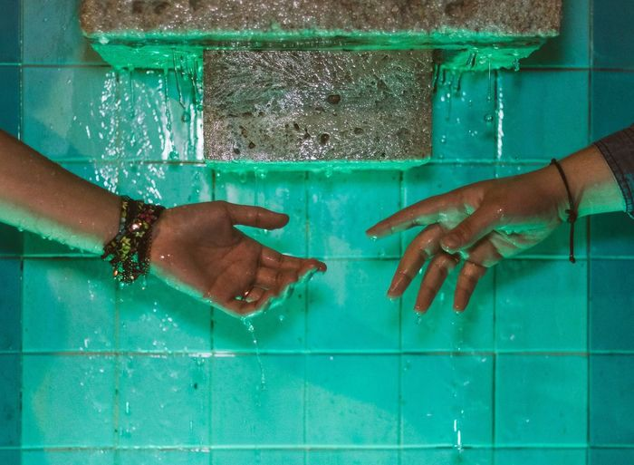 Cropped image of wet hands by wall