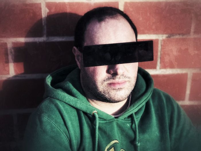 Portrait of man wearing 3-d glasses against brick wall