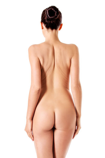 Rear view of naked young woman while standing against white background