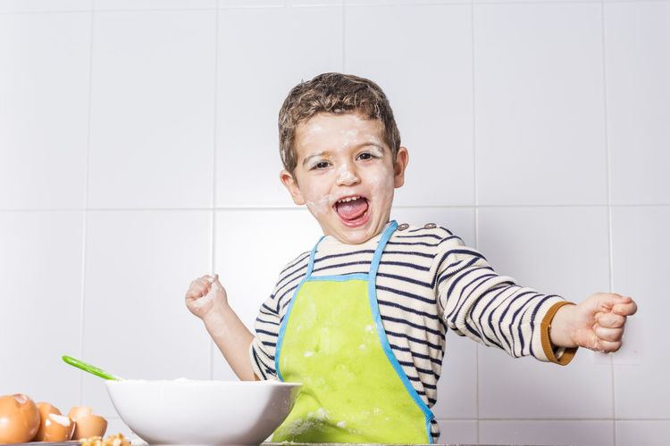 Portrait Of Excited Shouting Boy Wearing Apron Preparing Food At Home