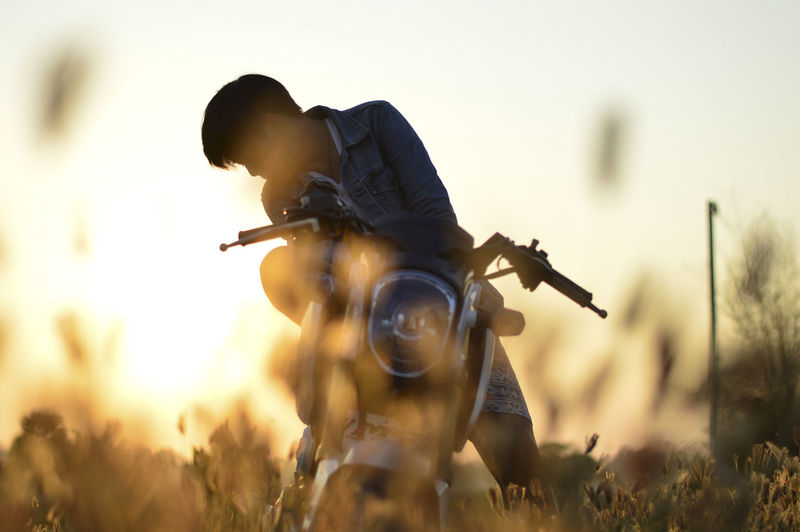 Young Man With Motorcycle On Field Against Sky During Sunset