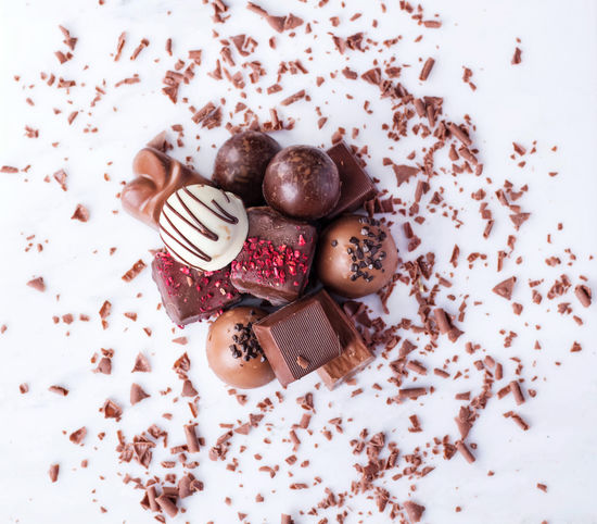 Traditional Belgian chocolate variety over rustic wooden board, decorated with chocolate swirls. Top view Background Backgrounds Belgium Chips Chocolate Dark Chocolate Milk Chocolate Praline Sweet Sweet Food Sweets Swirl Wooden
