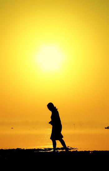 Silhouette woman walking at beach against orange sky