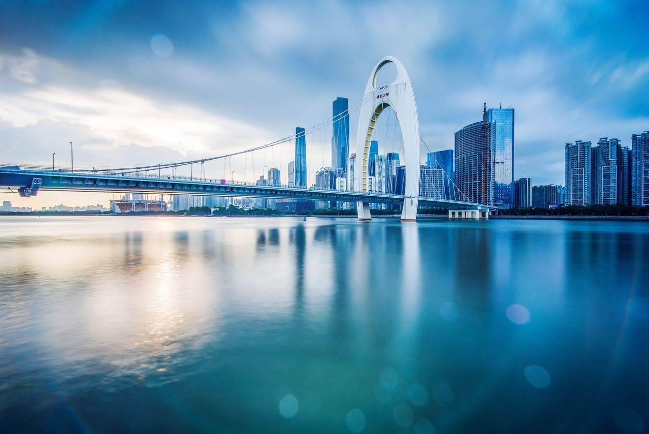 architecture, built structure, building exterior, bridge - man made structure, sky, connection, travel destinations, waterfront, water, city, no people, modern, cloud - sky, outdoors, skyscraper, day, cityscape, urban skyline