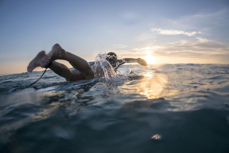 Man swimming in sea against sky during sunset