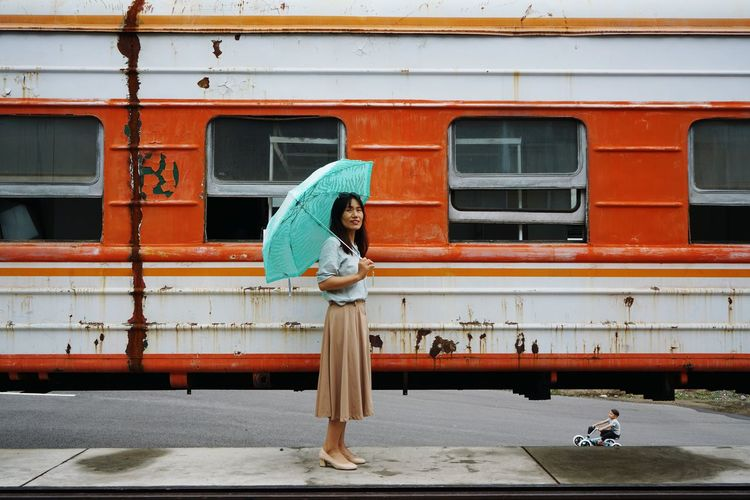 Side view of woman holding umbrella in city