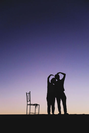 Silhouette couple making heart shape while standing against sky at dusk