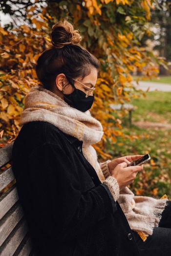 Woman wearing mask using smart phone sitting on bench