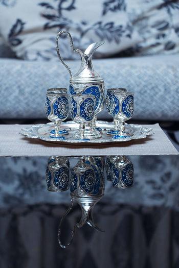 Metal jug with wineglasses on table