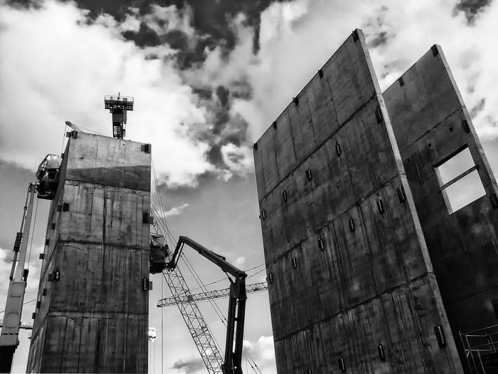 Low angle view of incomplete buildings at construction site against sky