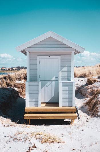 Wooden hut at skanör beach against clear blue sky.