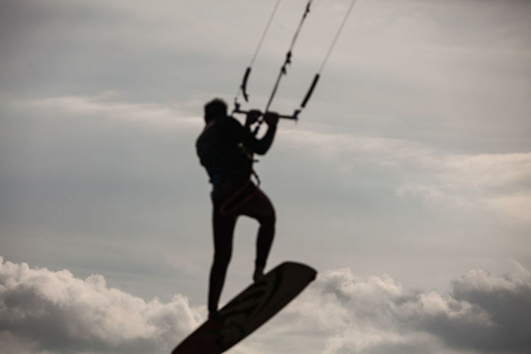 Low angle view of man holding rope against sky