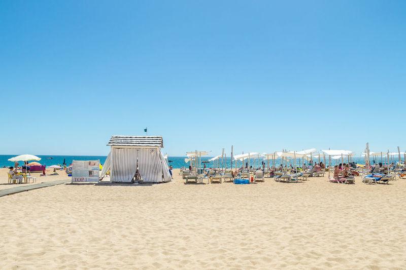 Hooded chairs on beach against clear blue sky