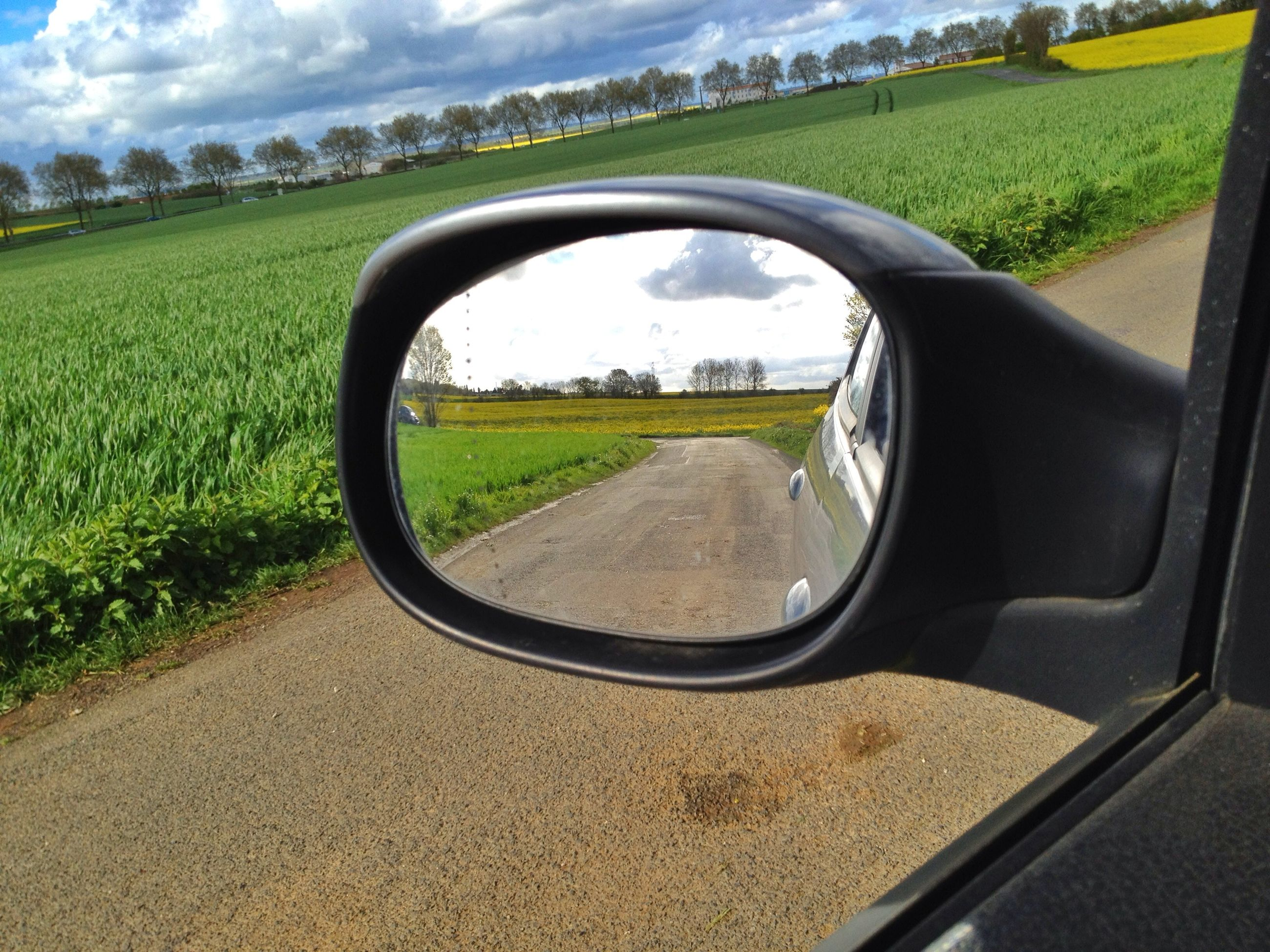 transportation, landscape, field, grass, sky, rural scene, road, land vehicle, side-view mirror, tree, mode of transport, car, nature, tranquil scene, cloud - sky, tranquility, grassy, countryside, scenics, day