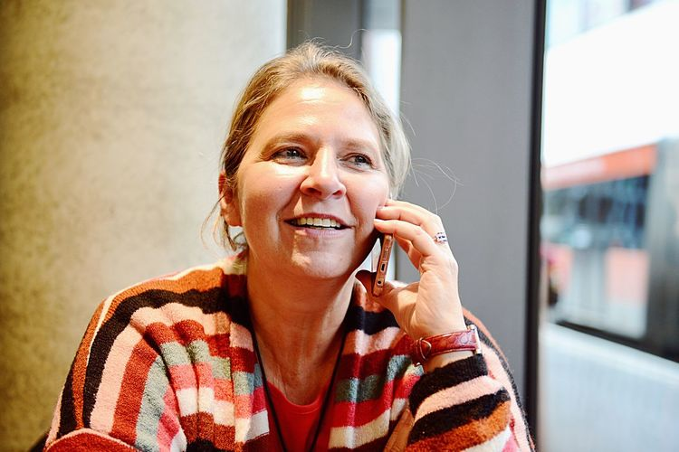 Close-up of mature woman talking on phone while sitting outdoors