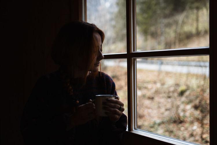 Woman drinking coffee in glass window