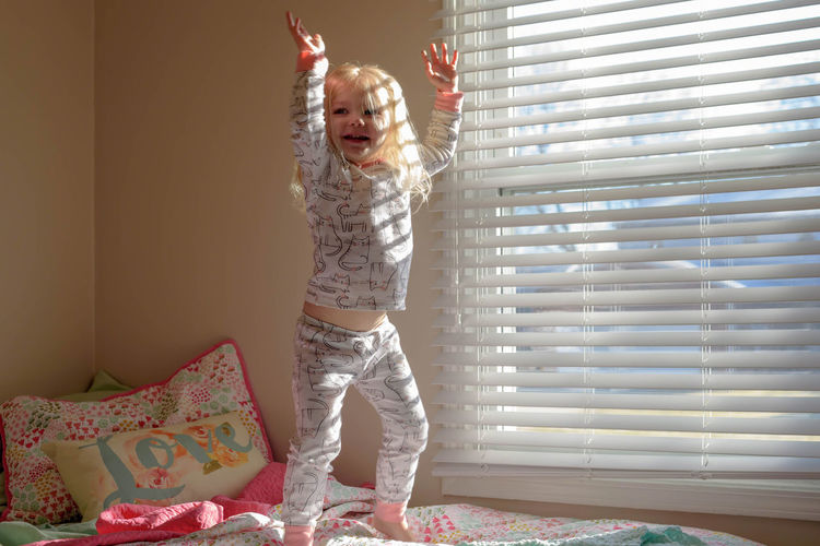 Cute blonde girl jumping on the bed in early morning light Cute Pets Family Fun Happy Happy People Kids Morning Natural Light Bedroom Childhood Cute Early Home Interior Joy Jumping Jumping On The Bed Lifestyles Little Girl Rise And Shine Smiling