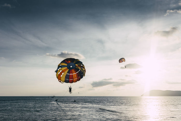 People Paragliding Over Sea Against Sky During Sunset