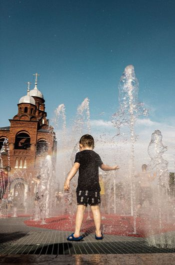 Rear view of boy looking at fountain in city against sky