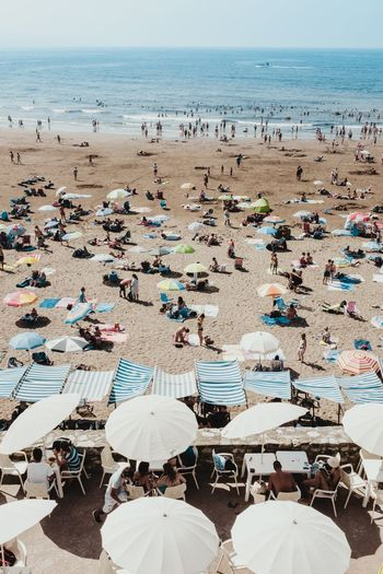 High angle view of people with parasols at beach during summer