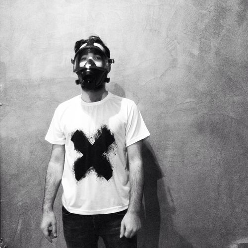 Portrait of man wearing gas mask while standing against wall