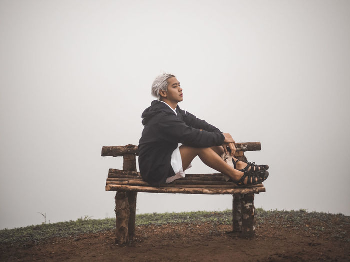 Young man looking away while sitting on bench