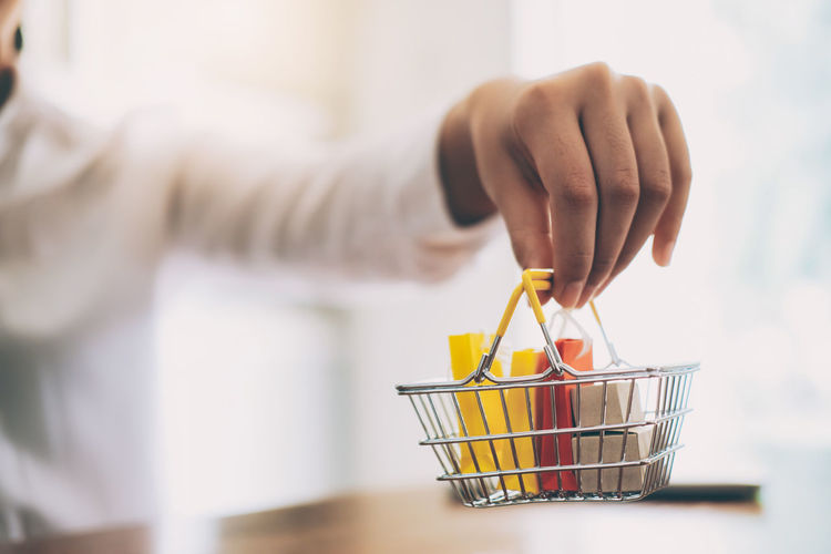 Cropped image of woman hand holding shopping basket with shopping bags