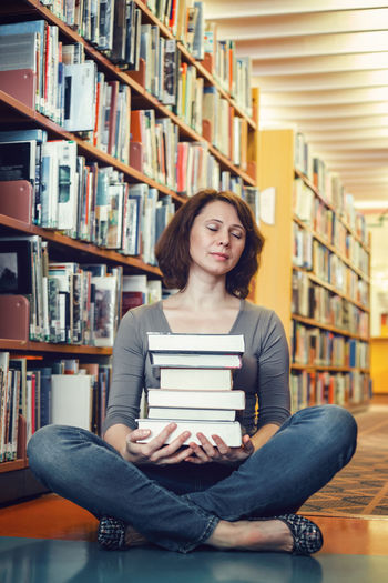 Portrait of young woman sitting on book