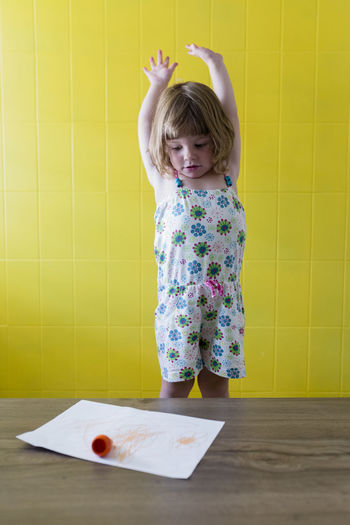 Cute girl with arms raised looking at paper on table