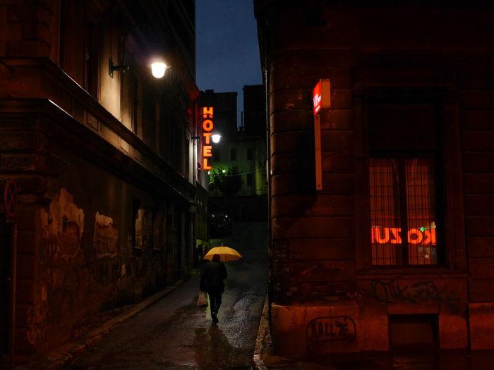 Man with yellow umbrella walking on illuminated street at night