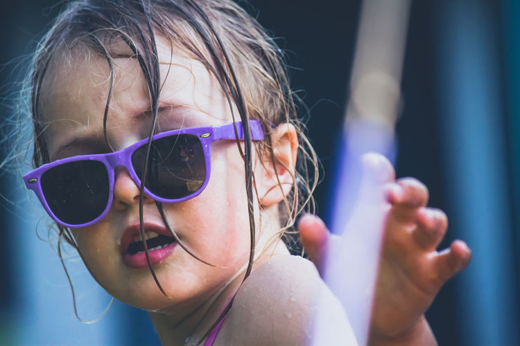 Close-up of portrait of cute girl wearing sunglasses