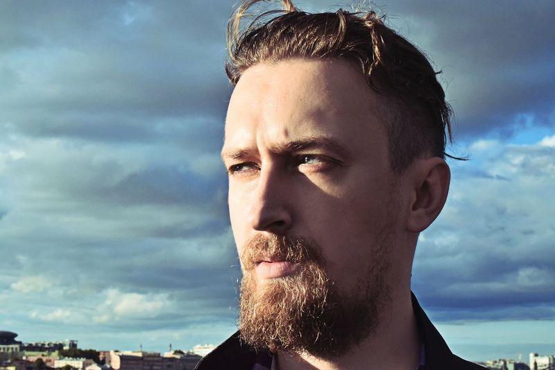 Bearded man looking away against cloudy sky