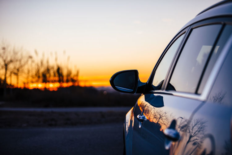Sunset Sky Transportation Mode Of Transportation Car Land Vehicle Nature Motor Vehicle Road Orange Color Reflection Copy Space Motion Outdoors Plant Travel Side-view Mirror on the move Scenics - Nature Clear Sky Road Trip