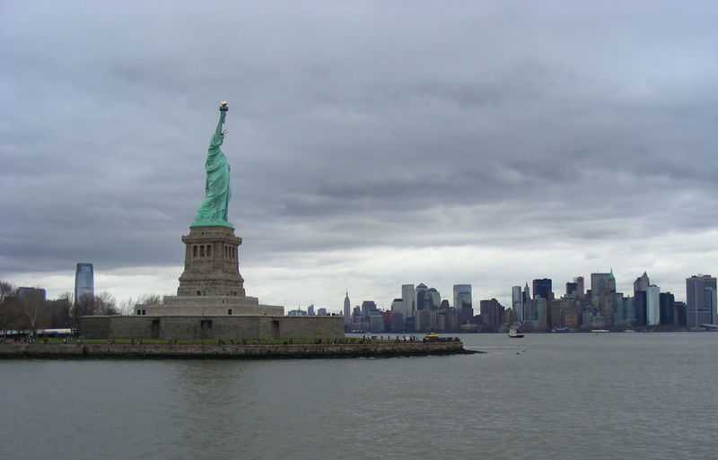 Statue of liberty and sea against cloudy sky