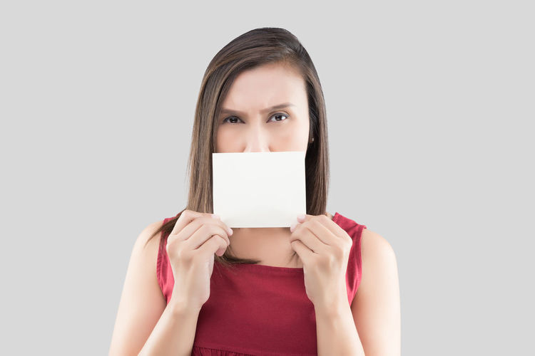 A woman in the red shirt holding the blank white card with space for text in front of his mouth against the gray background Showing Hand Grab Gestures Empty Holding Blank Catch Women Paper Mouth Close Halitosis