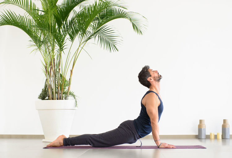 Side view of man exercising against wall