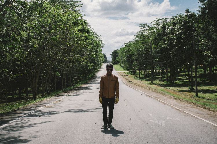 Man standing on road amidst trees