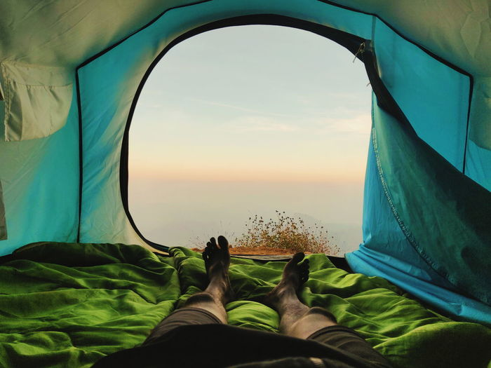 Low section of man relaxing in tent against sky during sunset