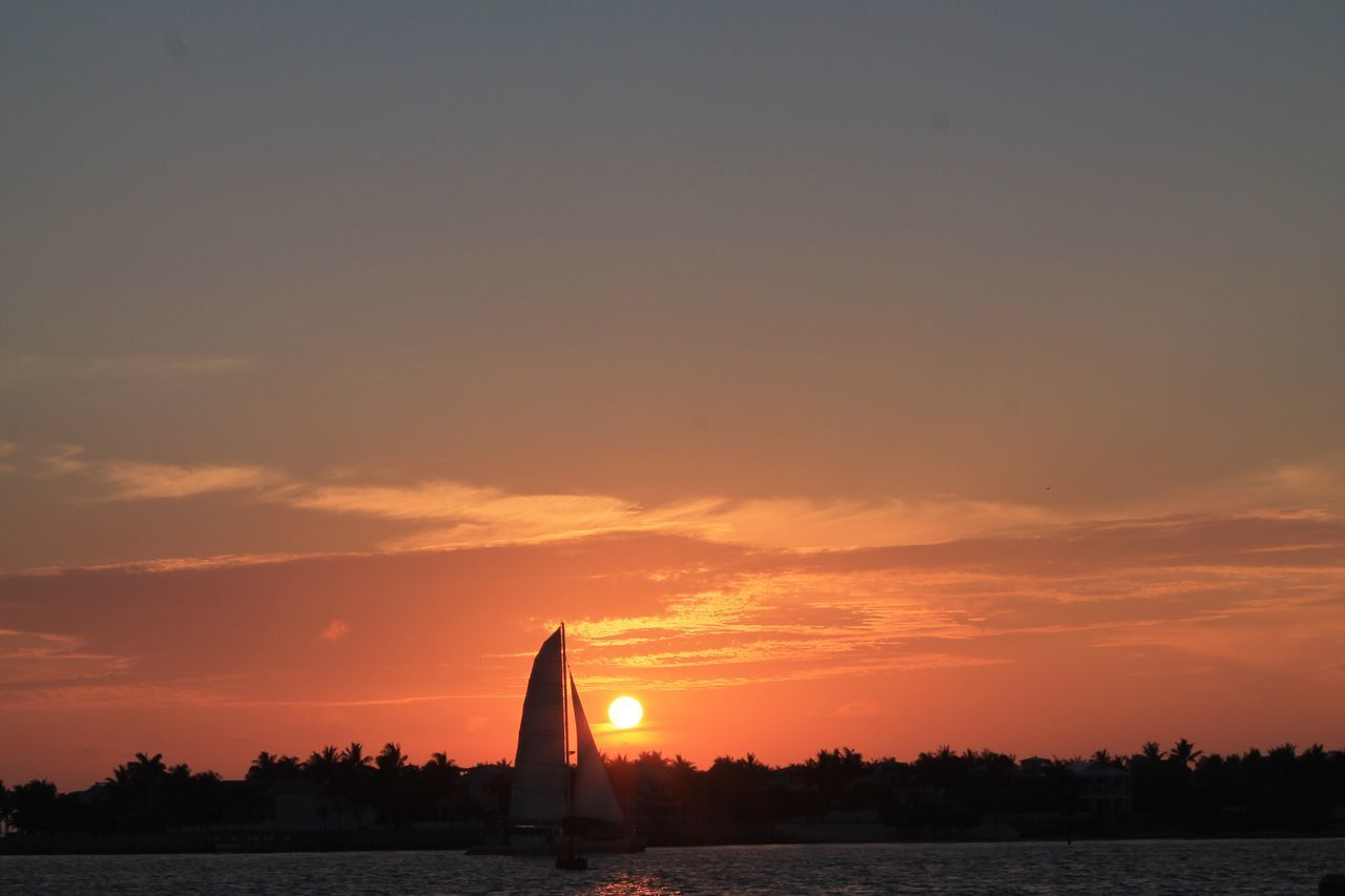 Scenic View Of Sunset Over Sea And Sailboat