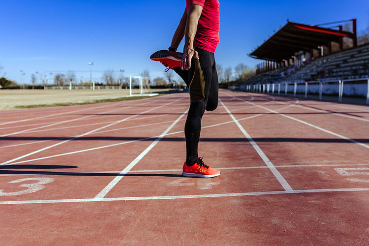 Low section of athlete exercising on sports track