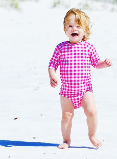 Portrait Of Baby Girl With Mouth Open Walking At Beach During Sunny Day