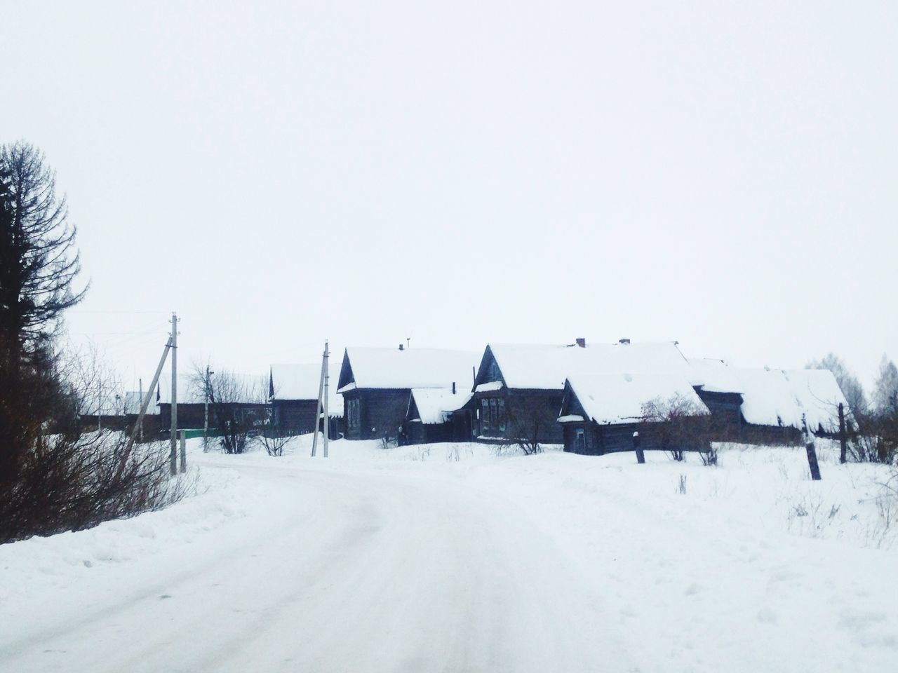 Snow Covered Houses On Field Against Sky