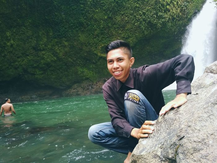 Smiling young man on rock by stream in forest